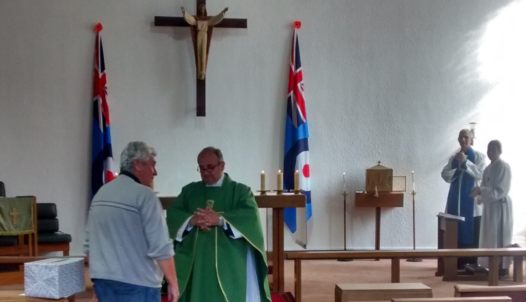 Father James and Tony infront of the congregation. The reader and altar boy look on.