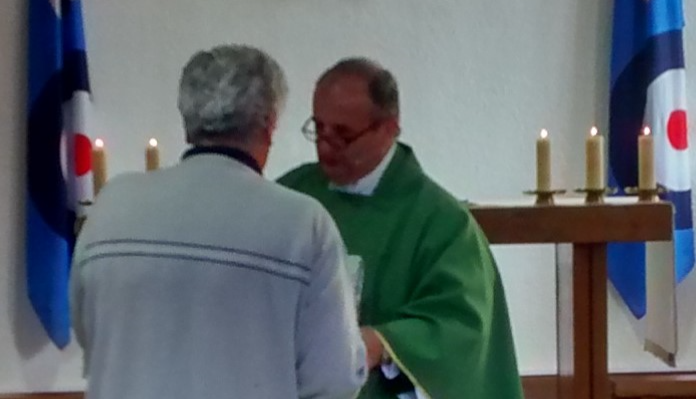 Father James presents Tony with a leaving gift infront of the congregation.
